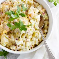 classic creamy potato salad in white bowl with spoon