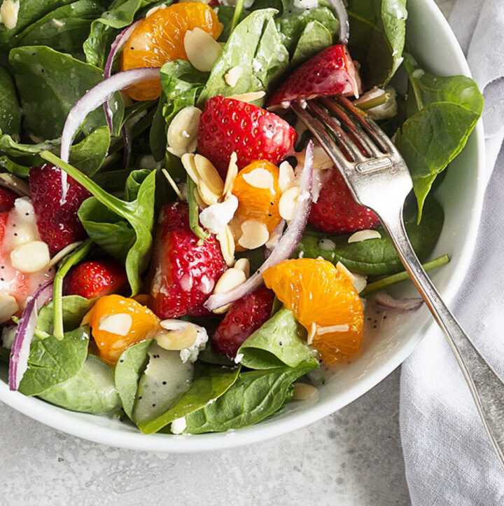 spinach strawberry salad in white bowl with fork