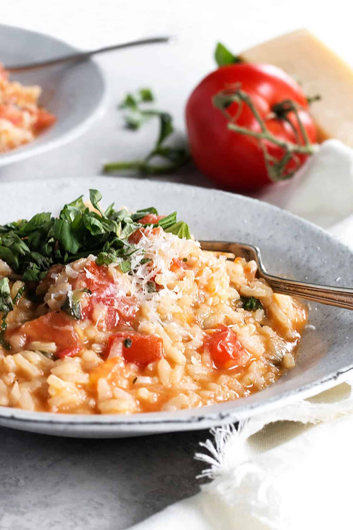 tomato risotto in bowl with whole tomatoes behind