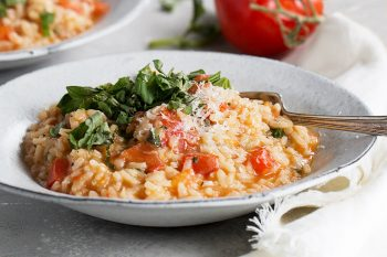 tomato risotto in bowl with basil and parmesan