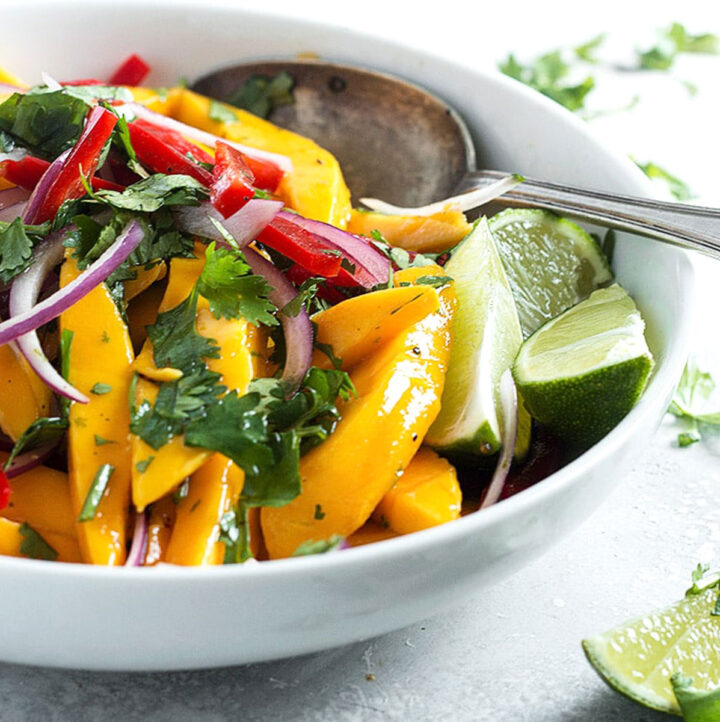 mango salad in white bowl with spoon