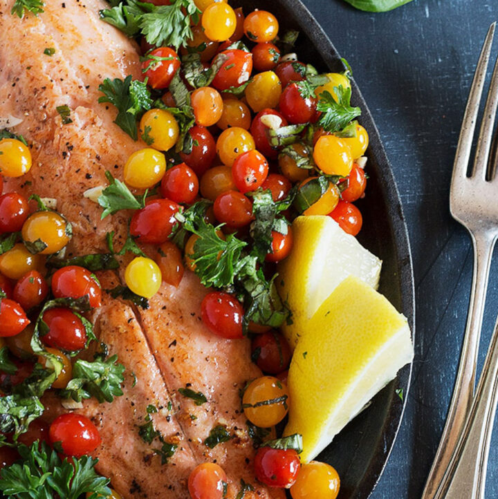 rainbow trout with mini cherry tomatoes in skillet