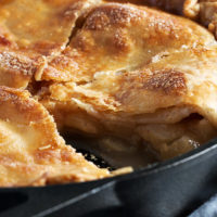 brown sugar peach pie in a skillet with one slice removed