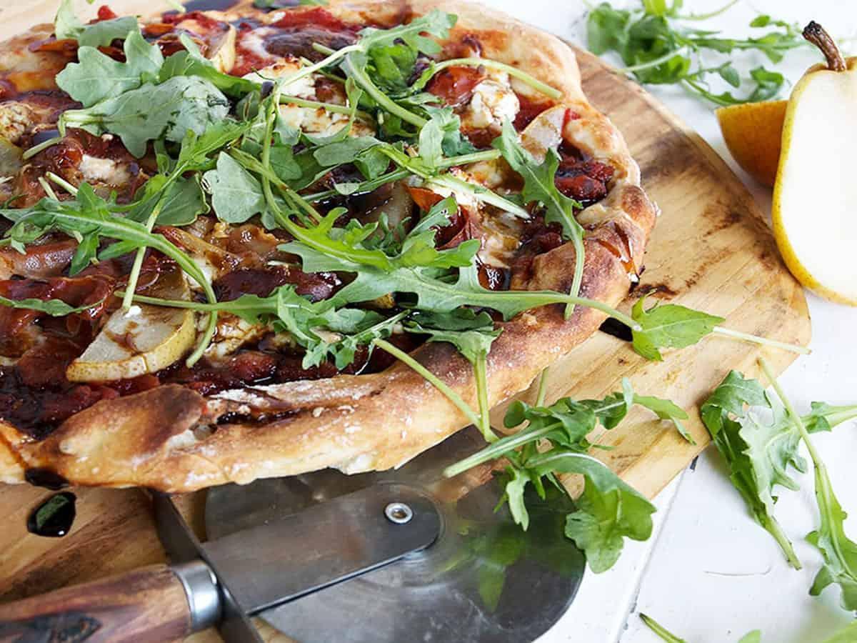 pear prosciutto pizza on pizza peel