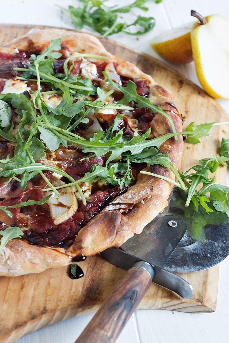 pear prosciutto pizza on a pizza peel