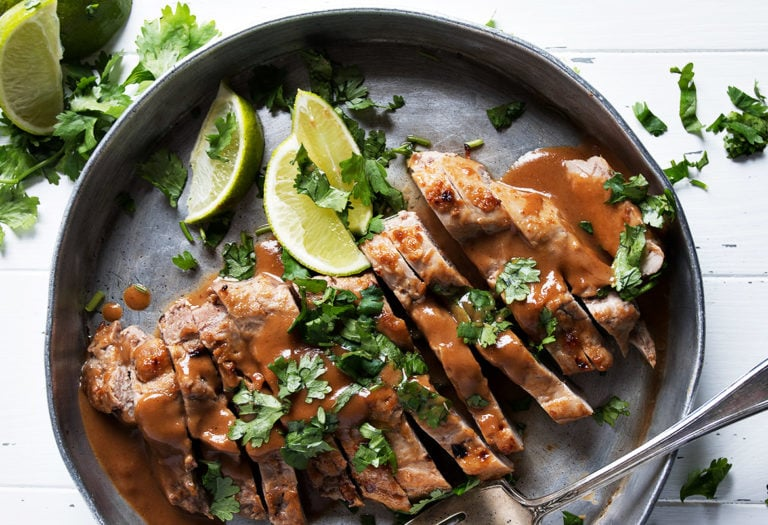 sliced pork tenderloin with peanut sauce and lime wedges