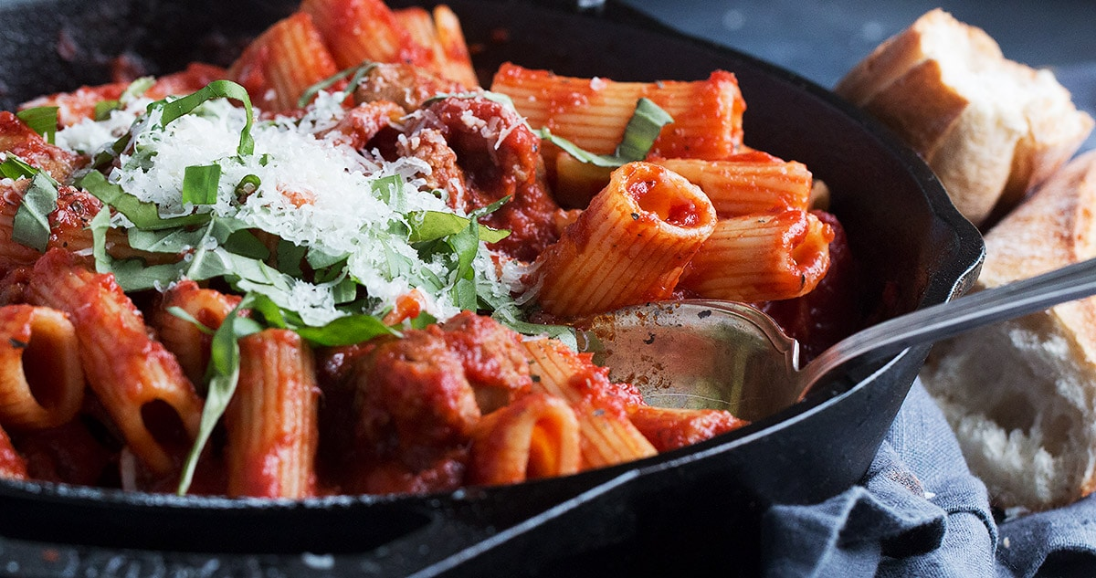 pasta with sausage tomato sauce in cast iron skillet