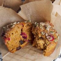 pumpkin cranberry muffins split open on parchment