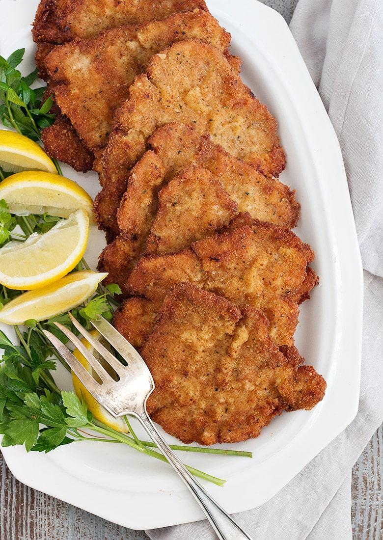 pork schnitzel on white plate with lemons