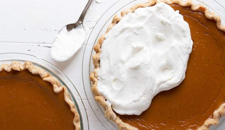pumpkin pie being topped with whipped cream