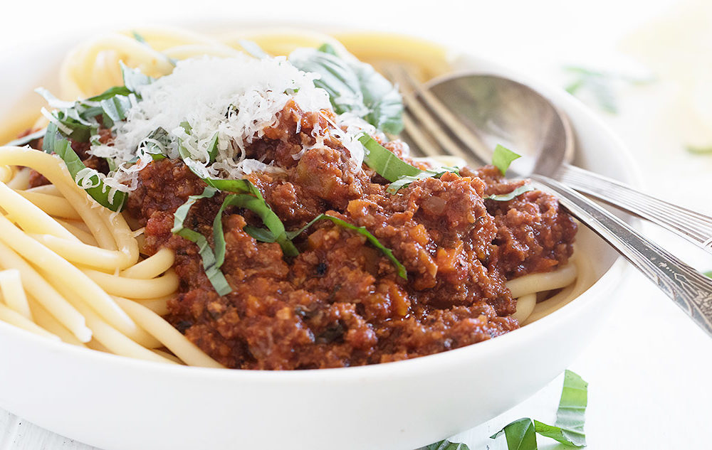 Italian meat sauce on pasta in a white bowl