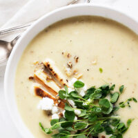parsnip and pear soup in white bowl with garnishes on top
