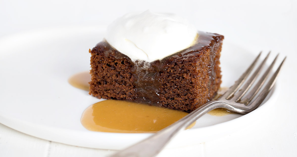 slice of gingerbread cake on white plate with whipped cream and toffee sauce