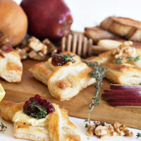 spreadable brie puff pastries with jam on cutting board