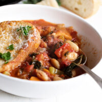 ribollita soup in white bowl with spoon
