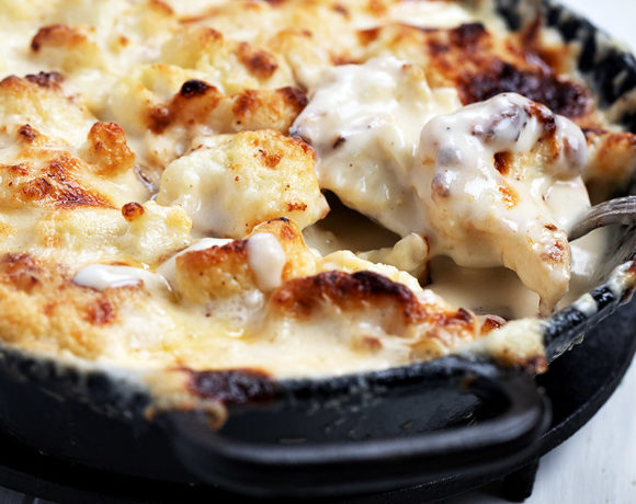 cauliflower cheese in cast iron dish with spoon