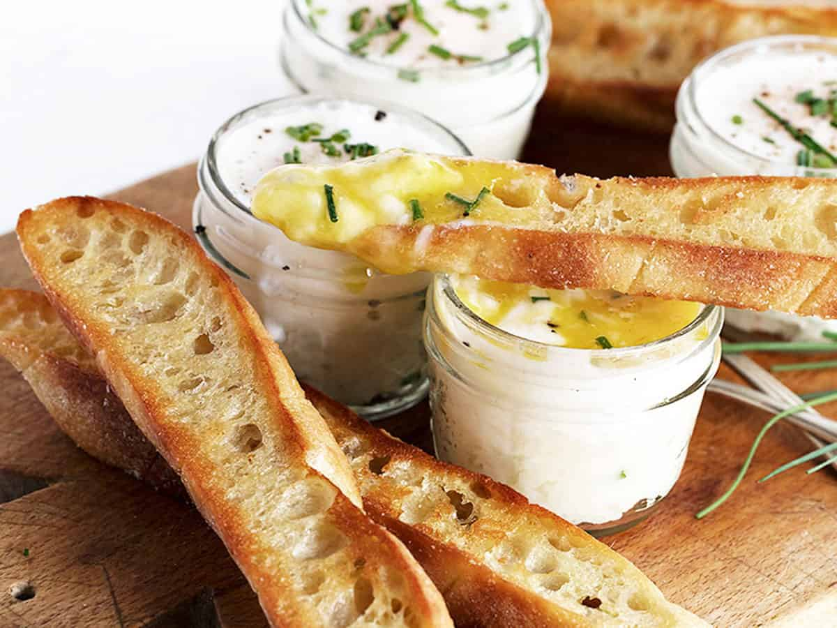 coddled eggs in small jars with mashed potatoes