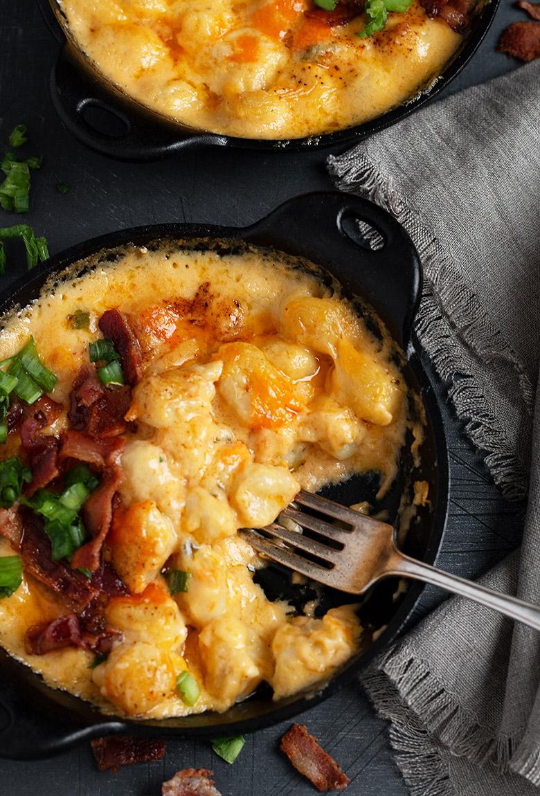 gnocchi and cheese in a small cast iron skillet with fork