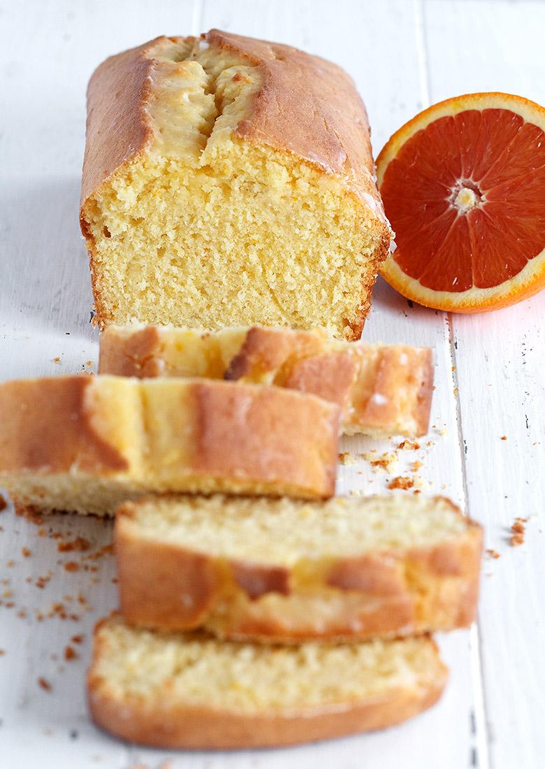 orange pound cake loaf sliced on white background with orange half
