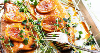 salmon on sheet pan with oranges on top