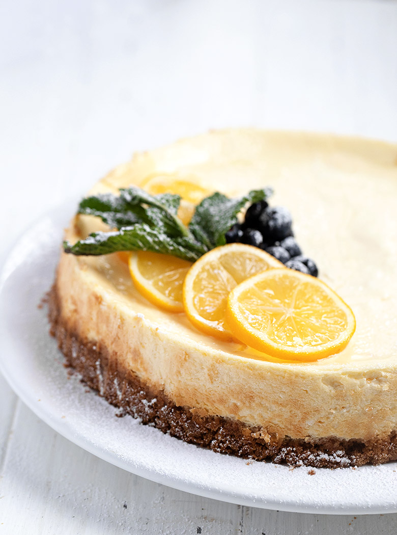 whole lemon cheesecake on white background garnished with lemons and blueberries