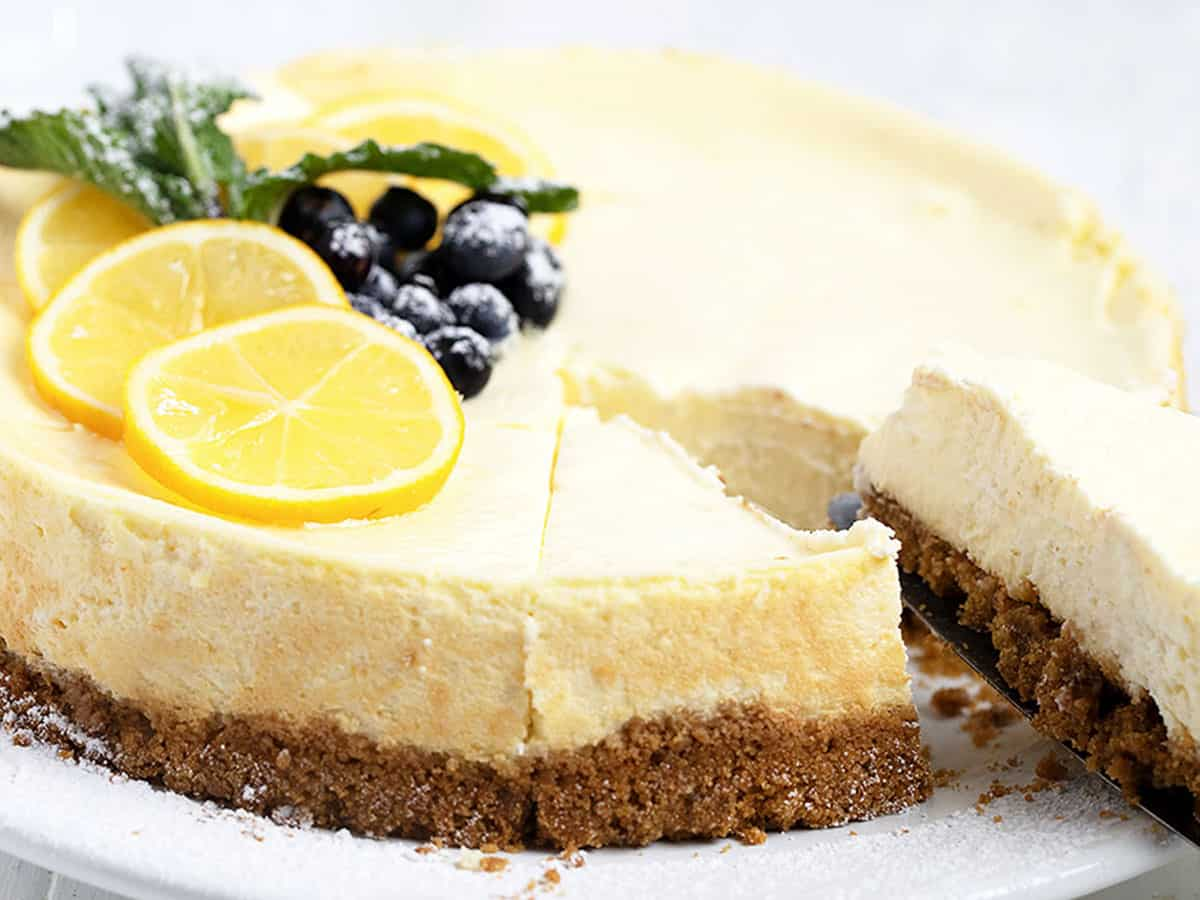 lemon cheesecake cut on plate with berries and lemon slices on top