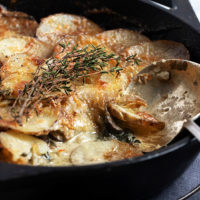 sliced potatoes and mushrooms in a cast iron skillet