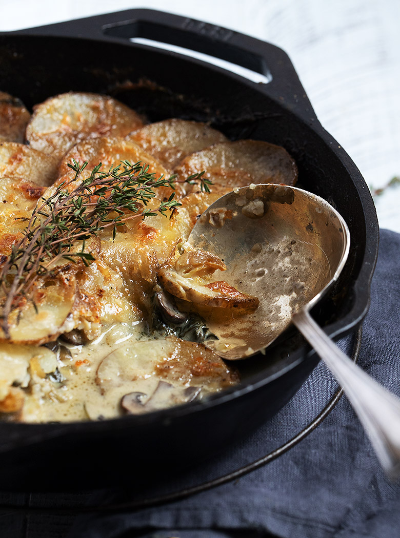 cheese topped potato slices and mushrooms in a cast iron skillet