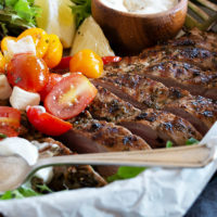 souvlaki pork tenderloin in platter with tomato salad and tzatziki