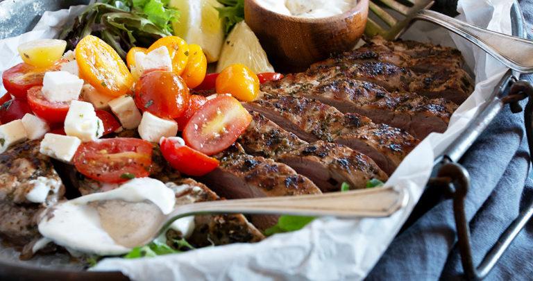 souvlaki pork tenderloin in platter with tomato salad and tzatziki