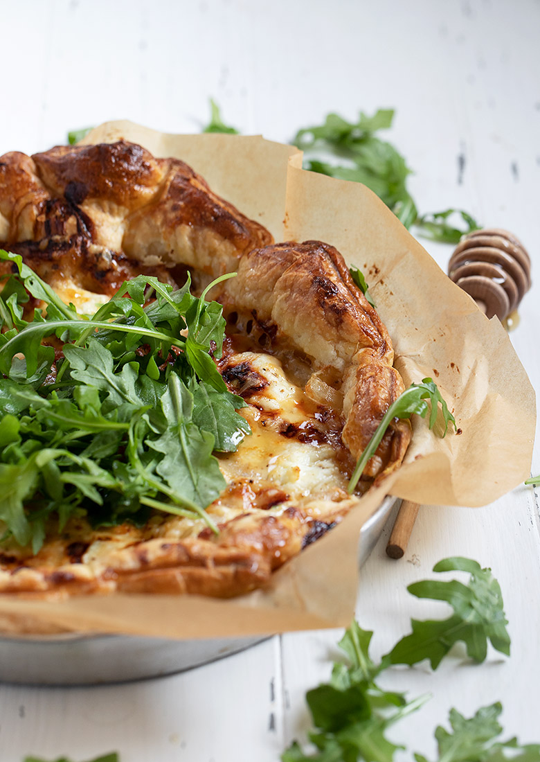 tarte au chevre topped with arugula and honey