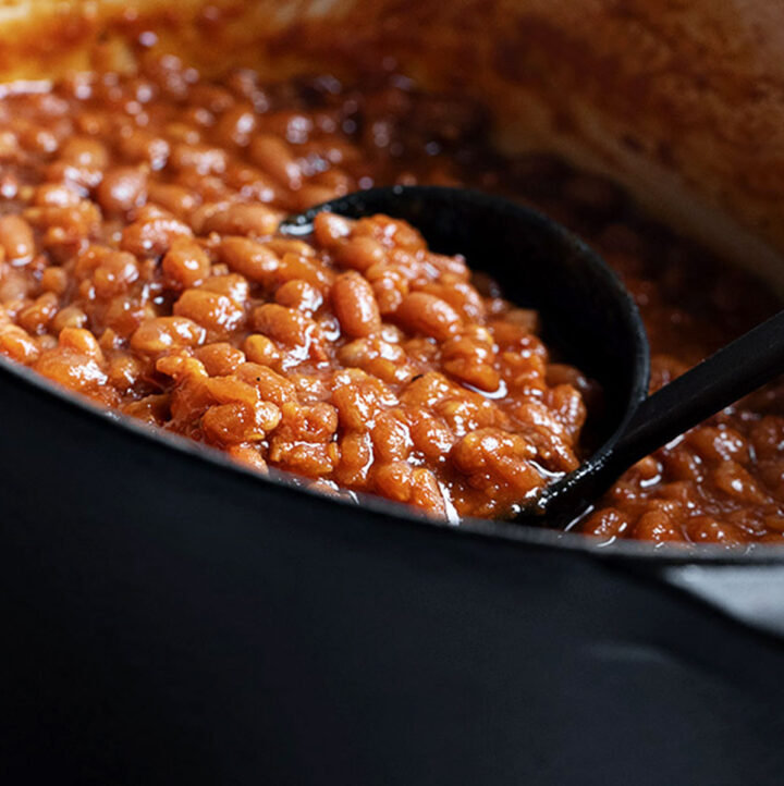 homemade baked beans in black casserole with ladle