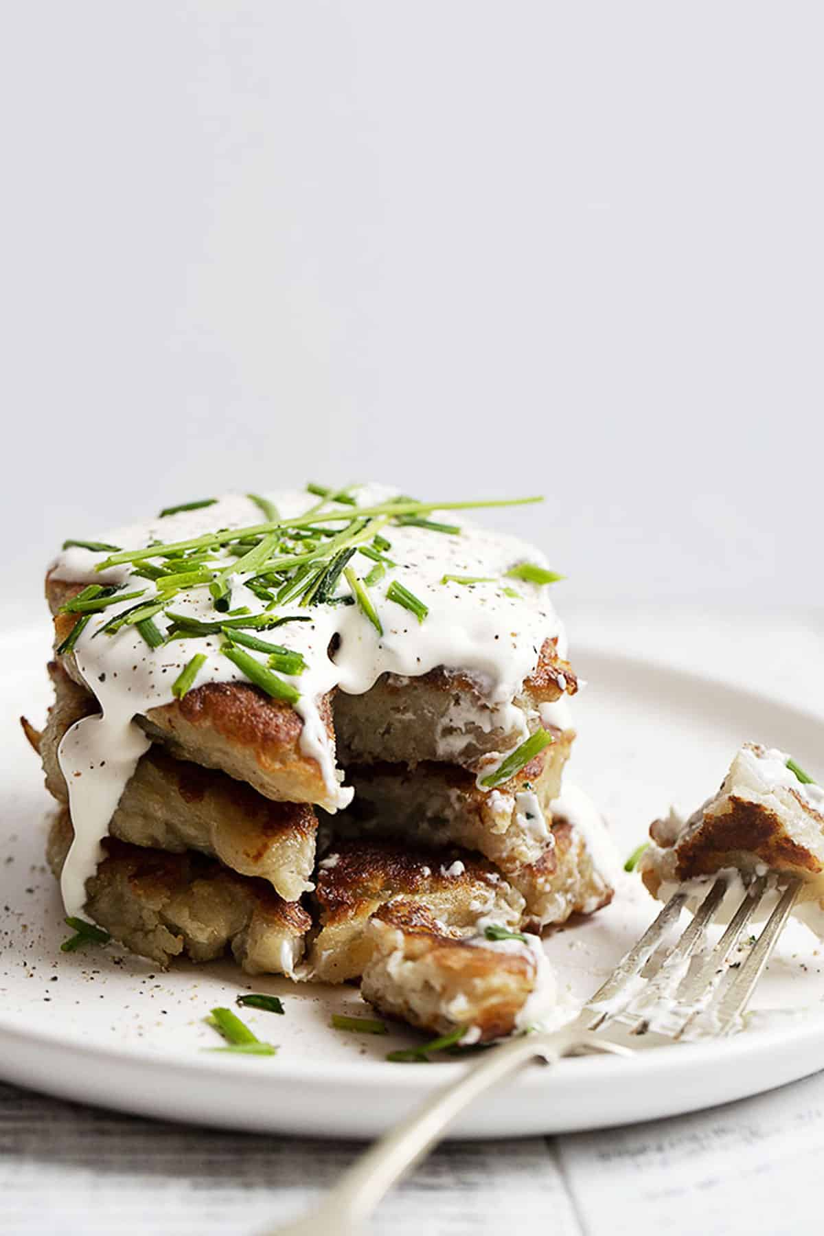 boxty stacked on a white plate with sour cream on top