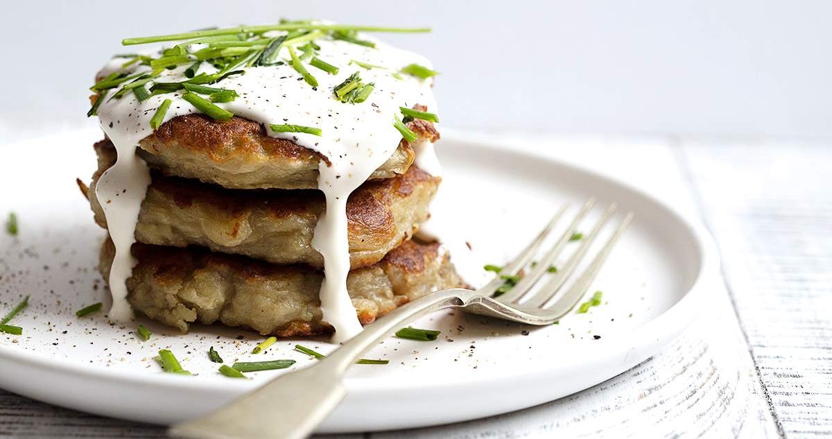 boxty Irish potato cakes on a white plate, topped with sour cream and chives