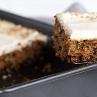 carrot sheet cake in pan with slice out