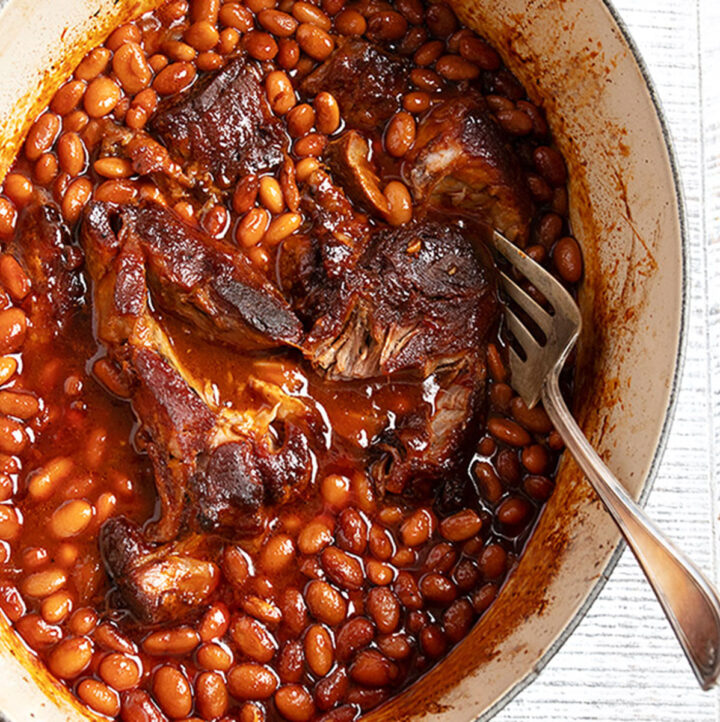 slow cooked pork and beans in casserole dish with spoon