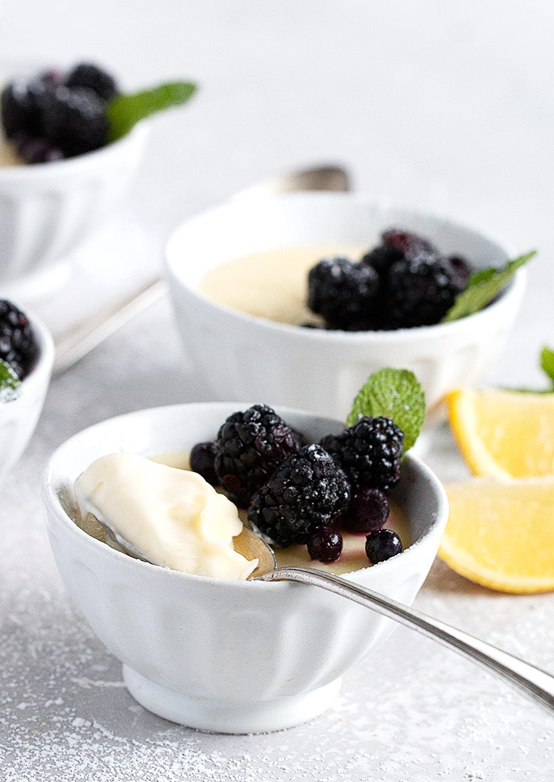 lemon posset is white bowls topped with blueberries and blackberries