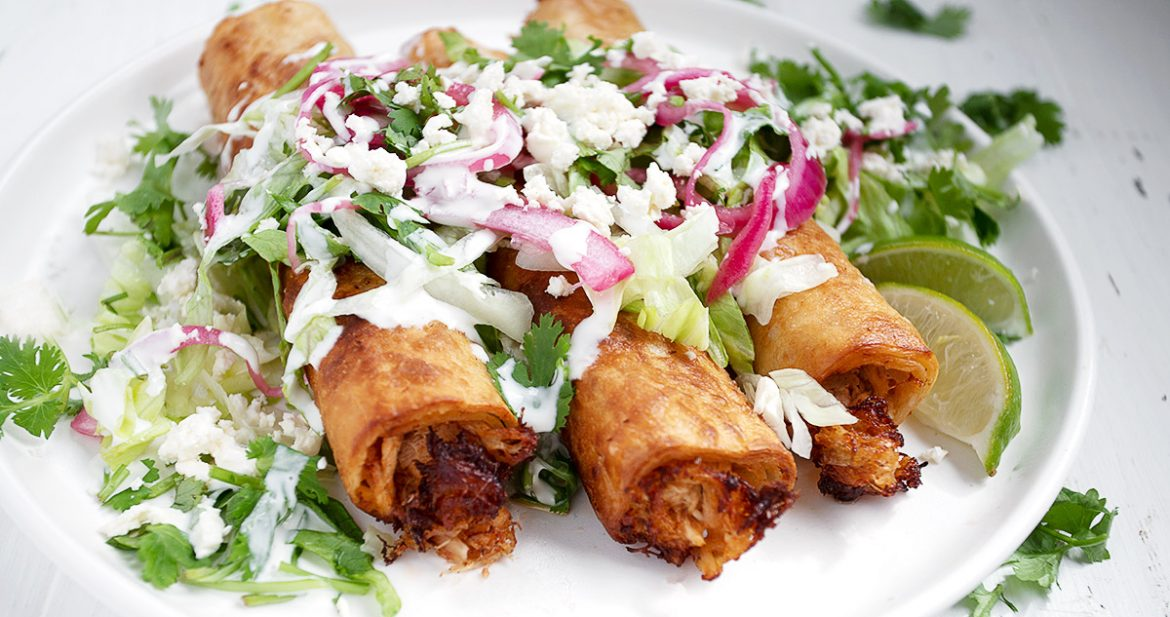 3 chicken flautas on white plate from front