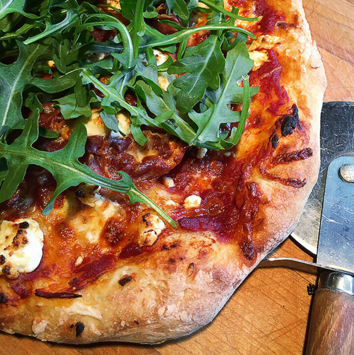 homemade gourmet pizza on cutting board with pizza cutter