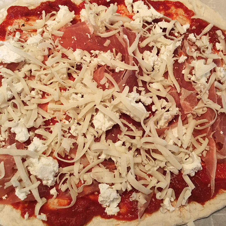 adding toppings to homemade pizza