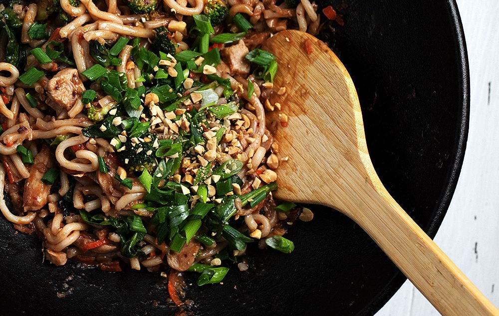 spicy peanut noodles in a cast iron wok with spoon