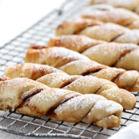 cinnamon twists lined up on a cooling rack in portrait view