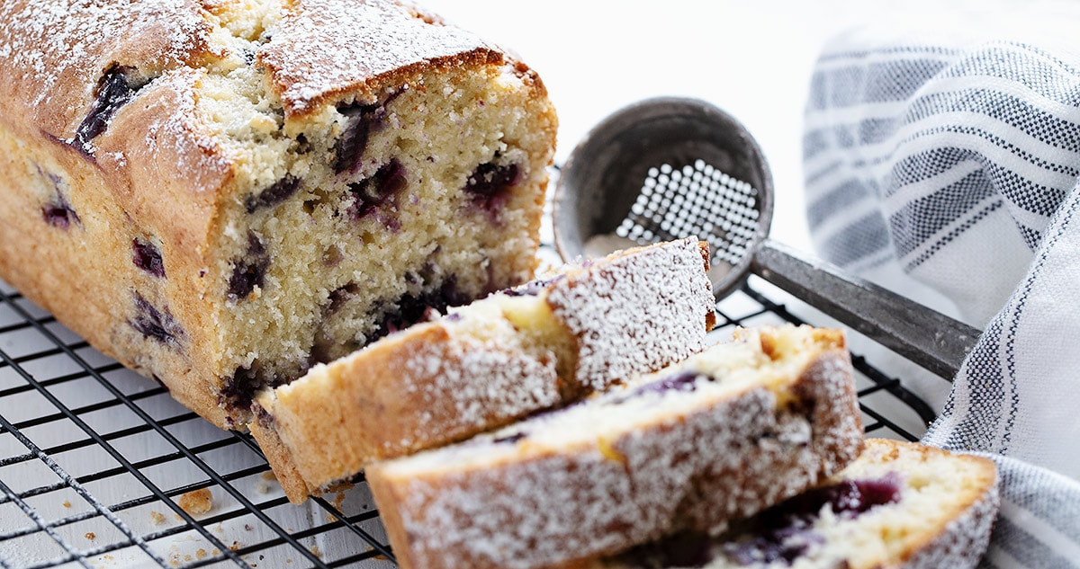 blueberry buttermilk loaf sliced on cooling rack landscape view