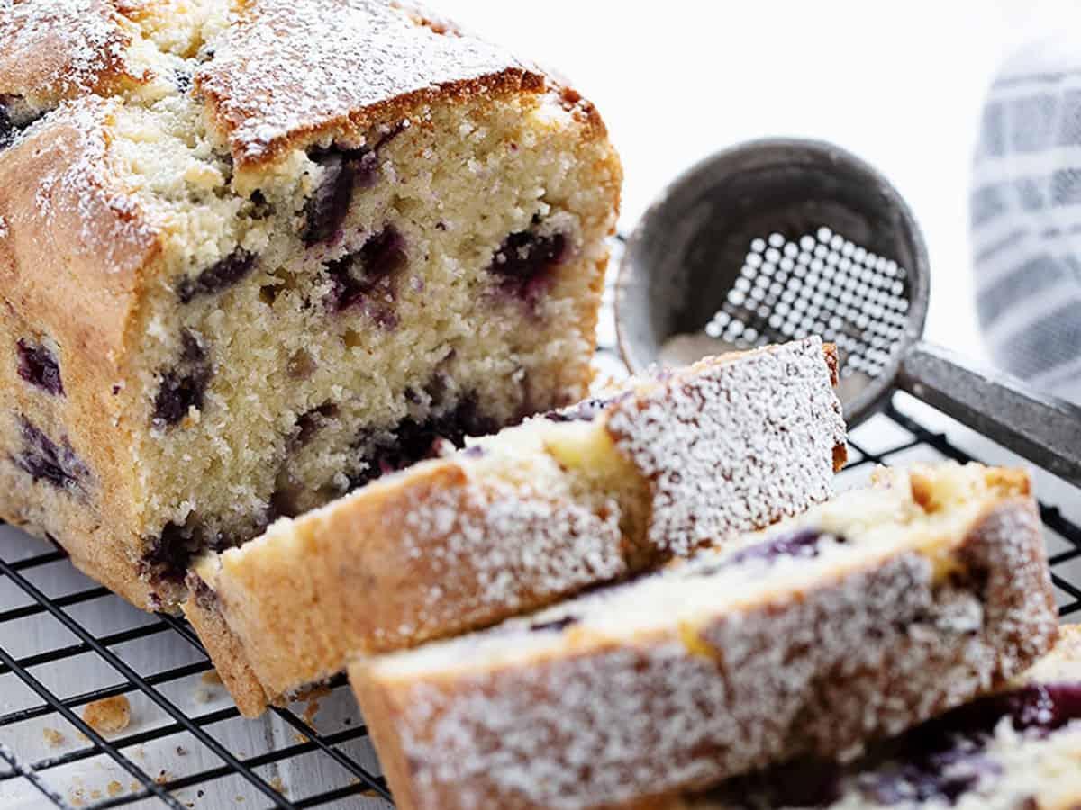 blueberry buttermilk loaf sliced on cooling rack