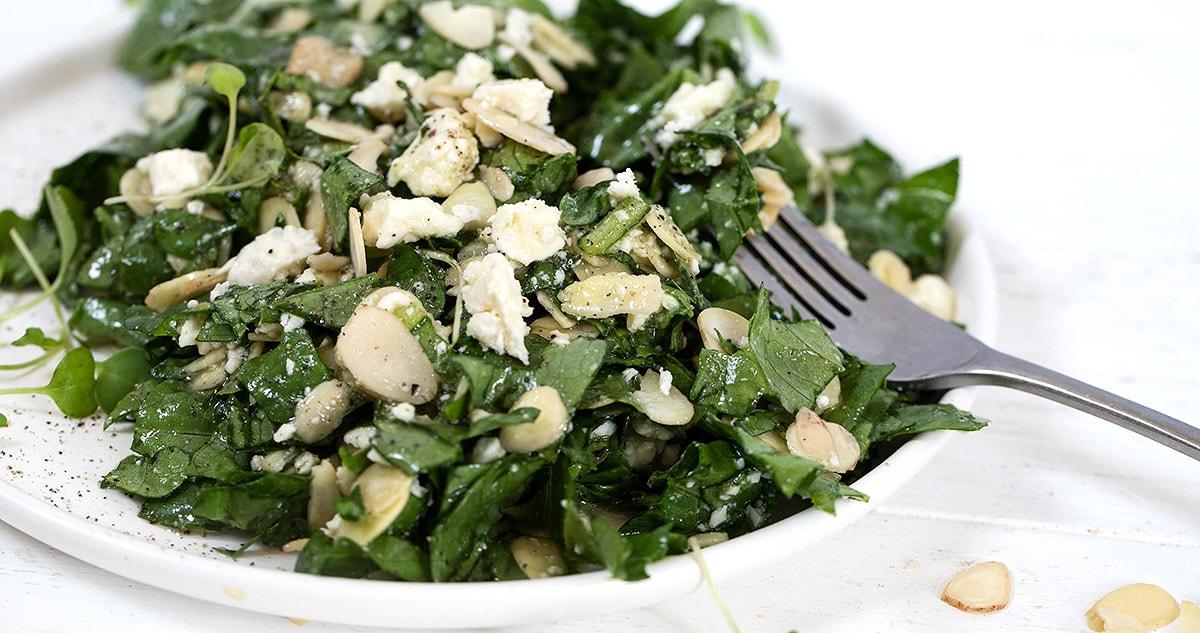 feta almond salad on white plate with fork landscape
