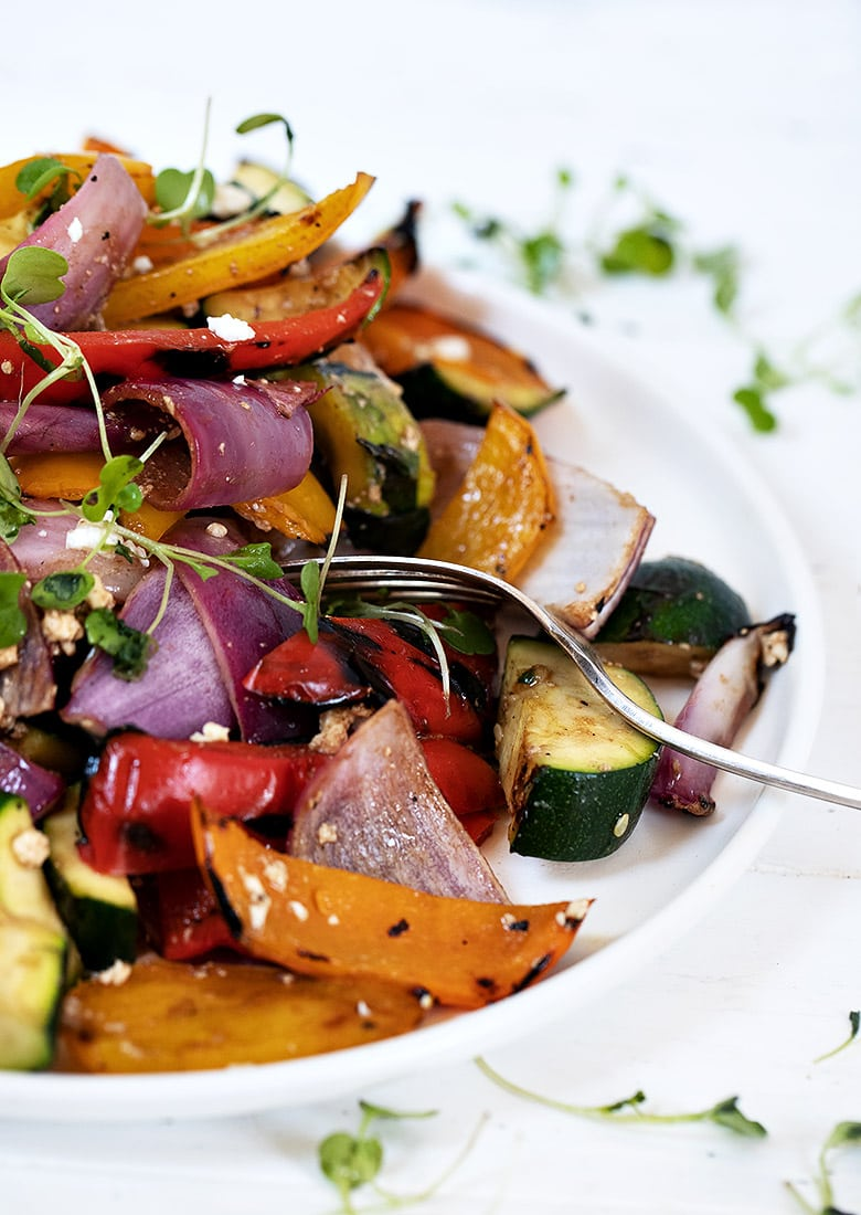 grilled vegetable salad on white plate portrait view