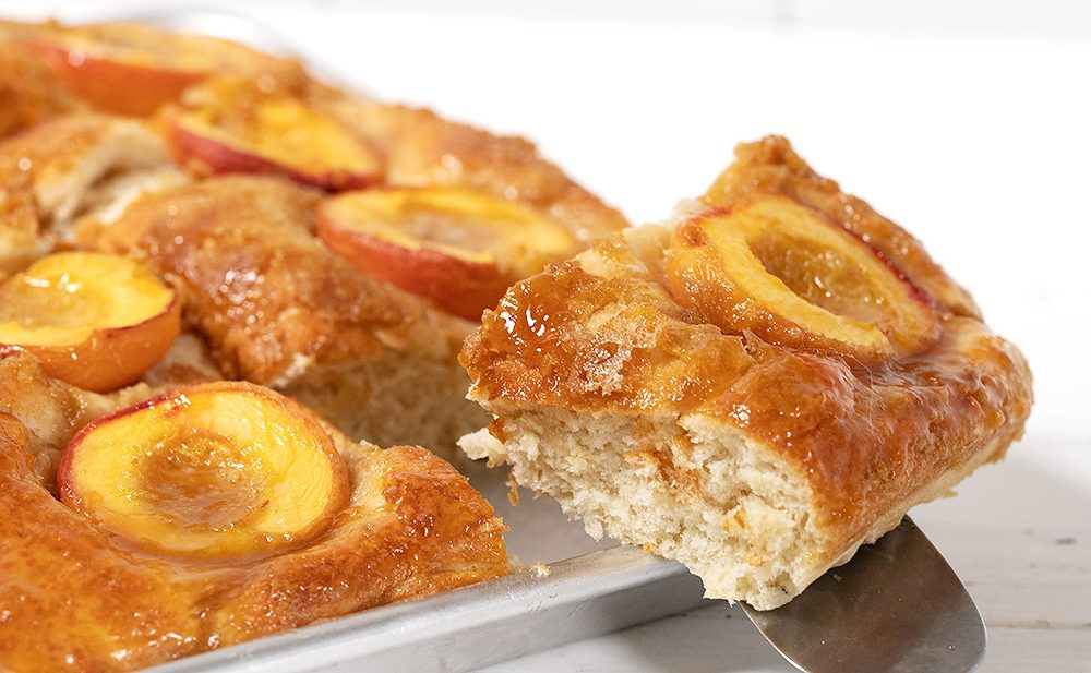 Baltimore peach cake in pan with slice