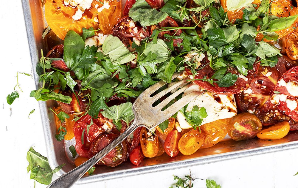 roasted heirloom tomatoes with feta on sheet pan with fork