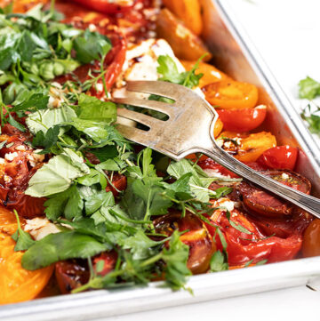 roasted heirloom tomatoes with feta and herbs on baking shee