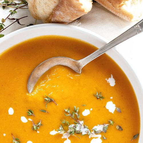 roasted butternut squash soup in white bowl with bread on the side